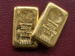 Two cast gold bars weighing 250 grams on the background texture burgundy leatherette