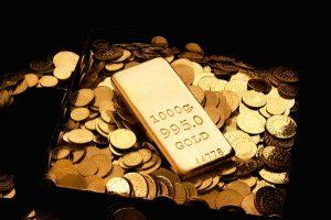 Gold bar atop gold coins