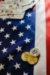 Bitcoin physical coins on American flag background with dollars
