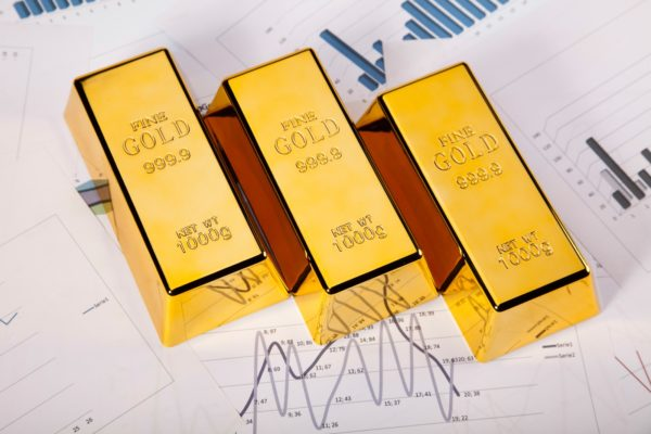 Three gold bars sitting atop financial documents