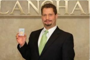 David Zanca, Senior Portfolio Manager, holding slabbed coin with Blanchard signage in background