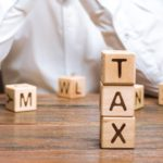 "Word ""TAX"" on wooden blocks with businessman in the background"