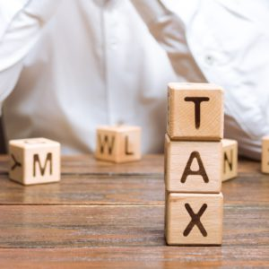 """Word """"TAX"""" on wooden blocks with businessman in the background"""
