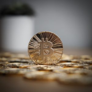 Digital currency physical metal bitcoin coin on the gold money background.